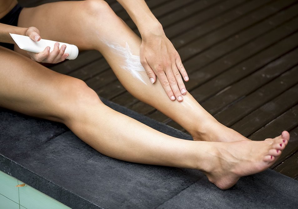 Cropped view of woman applying sunblock cream on her legs and sitting on terrace